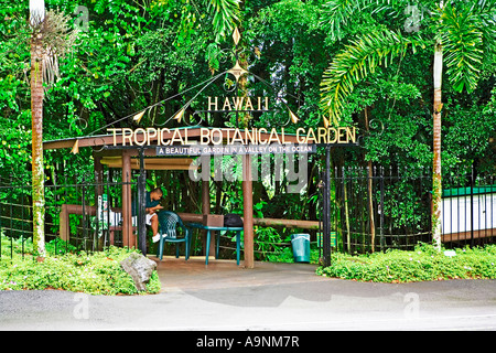 Imagen que muestra una de las puertas de entrada al jardín tropical cerca de Hawai con una joven Hilo Hawaiian esperando para saludar a los visitantes Foto de stock
