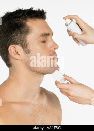El hombre tiene el agua pulverizada en su rostro.