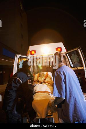 Paramédico y médico de ambulancia retirar al paciente