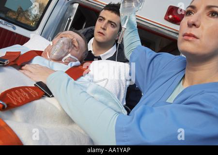 Paramédico y médico con el paciente en camilla