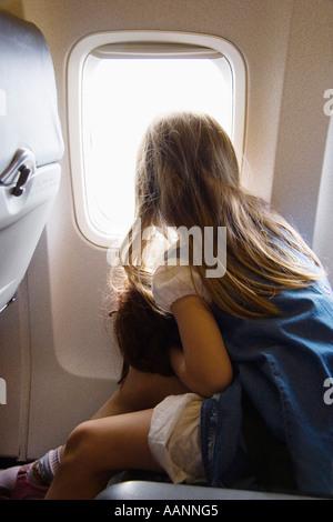 Niña con muñeca mirando por la ventana del avión