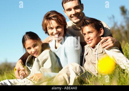 Familia sentado en la pradera
