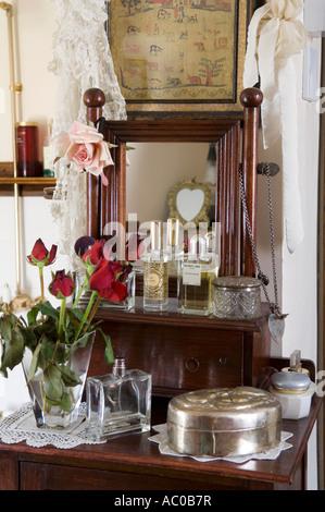 Rosas rojas sobre la mesita con frascos de perfume antiguos