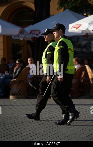 Dos oficiales de la policía de Polonia en patrulla en frente de la calle cafe en Rynek Glowny Town Square Cracovia