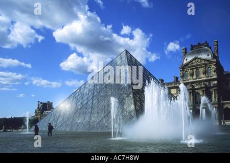 Museo Musee du Louvre y turistas disfrutan las fuentes alrededor de la pirámide en la primavera de SOL sol con el cielo azul y blanco clo