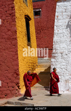 Los monjes tibetanos caminando por el ocre rojo y paredes pintadas de blanco el Monasterio Ganden Tibetano China