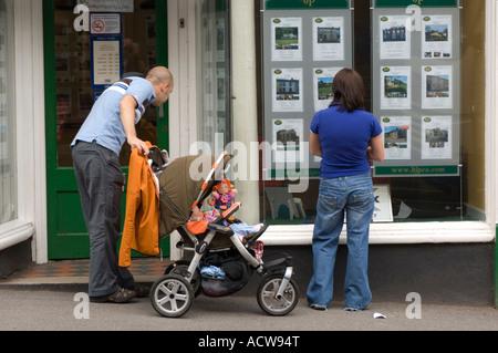 Pareja joven con el niño en el cochecito mirando house detalles de la propiedad inmobiliaria Llandeilo ventana Carmarthenshire Gales occidental UK