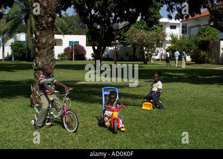 Los niños africanos locales jugando fuera de sus hogares en el desarrollo de vivienda con sus padres en el fondo Accra Ghana
