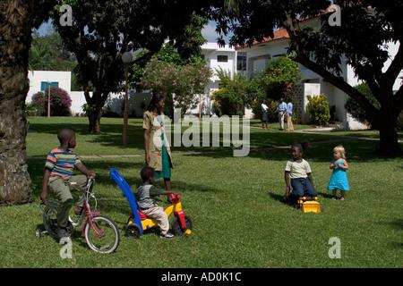 Los niños africanos negros con la madre y la niña blanca amigo jugando fuera de sus hogares en Accra, Ghana, África occidental
