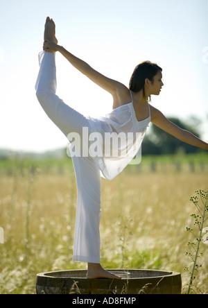 Mujer haciendo yoga plantea en el campo