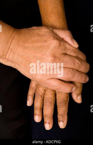 Un anciano hombre asiático coloca una mano sobre la mano de su esposa en una manera reconfortante.