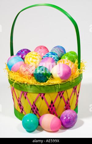 Paja cesta con huevos de Pascua de diferentes colores y patrones contra un fondo blanco.