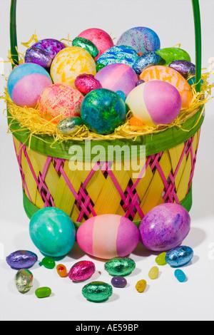 Canasta llena de huevos de color chocolate y dulces en la paja