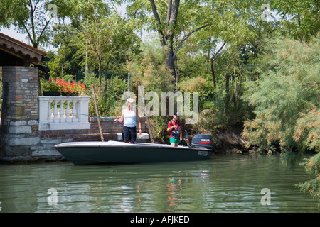 Hombre y niño en pequeñas lanchas de pesca en el canal de la isla de Torcello Italia