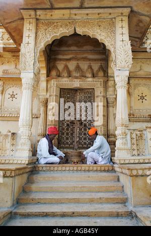Dos hombres jugando un juego tradicional hindú Chopar delante del templo de Siva en el lago Gadisar Foto de stock