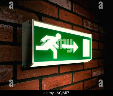 Hombre corriendo a la señal de salida de emergencia en una pared de ladrillo