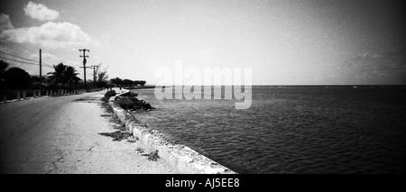 Imagen en blanco y negro fuera de una marina, mirando hacia abajo una antigua carretera vacía que se extiende a lo largo de la orilla del mar