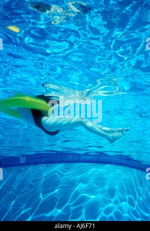 Vista submarina de la mujer en la piscina flotando en la vida liberada de la imagen modelo de anillo Foto de stock