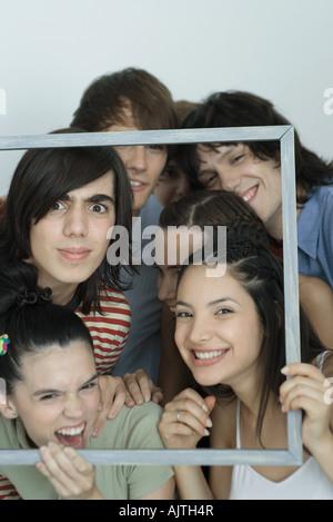 Grupo de jóvenes amigos posando para la foto, sujetando el marco de imagen, sonriendo a la cámara, Retrato