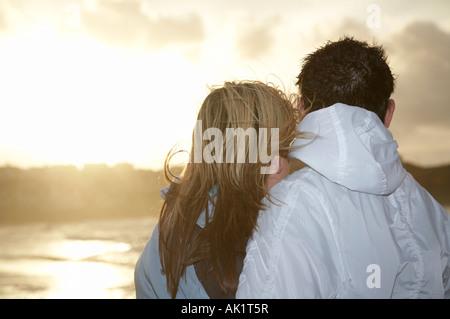 Pareja joven de pie abrazando mirando al mar junto a la costa en la puesta de sol sobre la costa Foto de stock