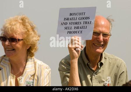 Hombre de mediana edad sosteniendo un cartel pidiendo un boicot israelí de producir