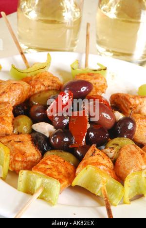 Tapas de estilo español de pollo, aceite de oliva y pimienta, pinchitos, marinados con aceitunas