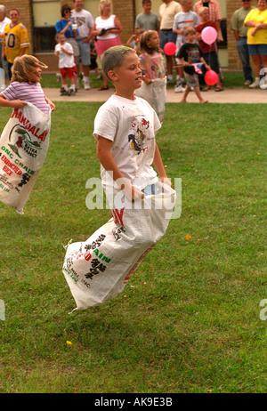 Los niños menores de 11 en la carrera de sacos de patatas en el Festival Días de sandía. Vining Minnesota USA Foto de stock
