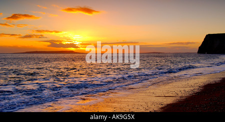 Puesta de sol en la costa de Dorset Swyre mirando al occidente desde la cabeza hacia los murciélagos de cabeza y la Isla de Portland en el horizonte