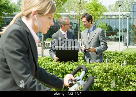 Mujer en bicicleta, dos hombres de negocios al fondo