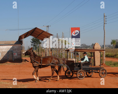 Viejo Estilo de Menonitas en el Paraguay, el muchacho con el típico carro de caballos en frente de una estación de gas