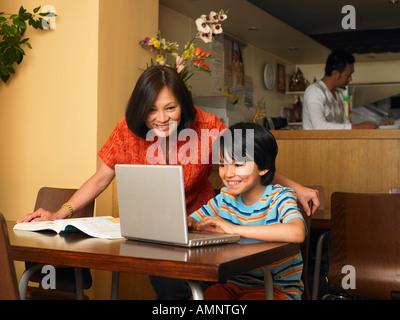 Niño y Madre con los deberes en restaurante.