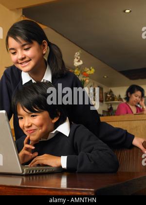 Chico y chica con deberes en restaurante.