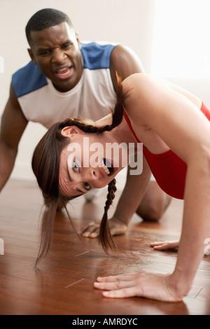 Mujer haciendo flexiones con entrenador