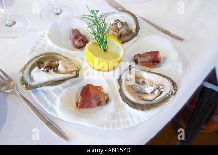 Las ostras en dos modas: fresca y laminado en tocino con un limón y el romero en una placa blanca en un conjunto mesa de comedor del lujoso Hotel Excelsior y Spa Restaurant Terraza Dubrovnik, ciudad vieja. La Costa Dálmata, Croacia, Europa.