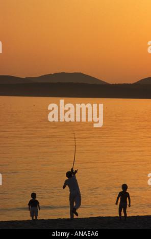 Padre e hijos de pesca en la Riviera del Corallo, Cerdeña, Italia