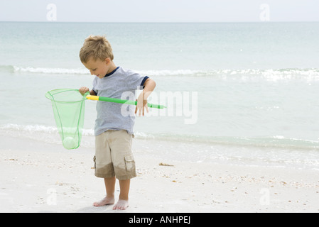 Joven de pie en la playa, sosteniendo la bola en net, mirando hacia abajo