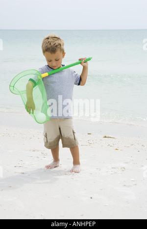 Joven de pie en la playa, alcanzando para pelota en net