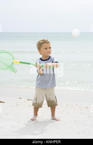 Joven de pie en la playa, sujetando net para atrapar la bola