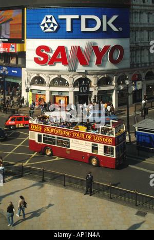 Vista aérea semi open top bus tour en Piccadilly Circus pasando publicidad iluminada acaparamiento