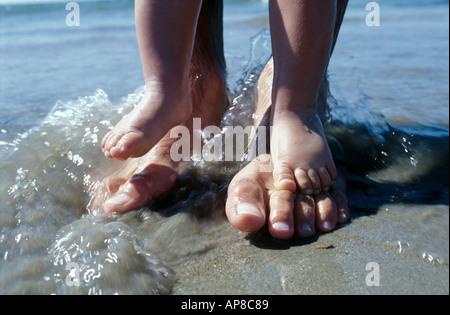 Los pies del Padre y del hijo en la playa más cerca