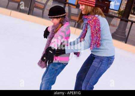 Una madre que ayudaba a su hija mientras que el patinaje sobre hielo en Northstar ski resort, cerca del Lago Tahoe en California