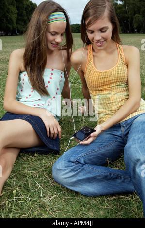 Dos chicas adolescentes escuchando música desde el reproductor de mp3 Foto de stock
