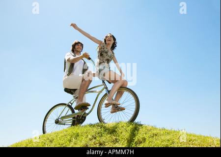 Pareja joven en bicicleta por Hill (ángulo de visión baja)
