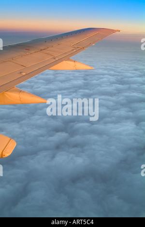 Ala de avión jet volando por encima de las nubes a Sunise