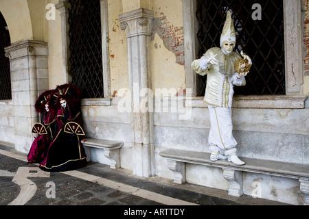 Un hombre en traje de Carnaval y máscara de equilibrio sobre un banco de piedra siendo observados por dos mujer Foto de stock