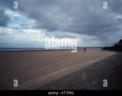 Adulto y joven caminando por la playa, la Bahía de Dublín, Irlanda Foto de stock