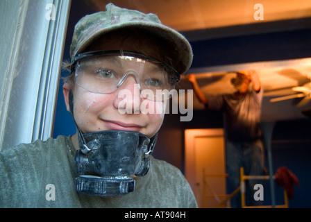 Inicio Los trabajos de construcción. Adolescente llevaba una máscara ventalation mientras ayudan a raspar el techo con antiguos hombre afroamericano