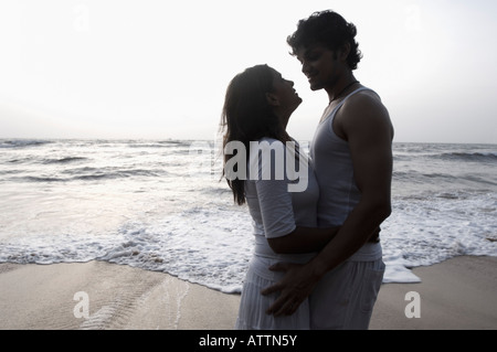 Silueta de una joven pareja abrazándose entre otros en la playa, Goa, India
