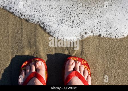 Dos pies vestidos de rojo flipflops stand en water's edge