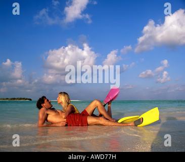 Pareja joven con equipo de snorkel en aguas poco profundas, playa, Maldivas, Océano Índico